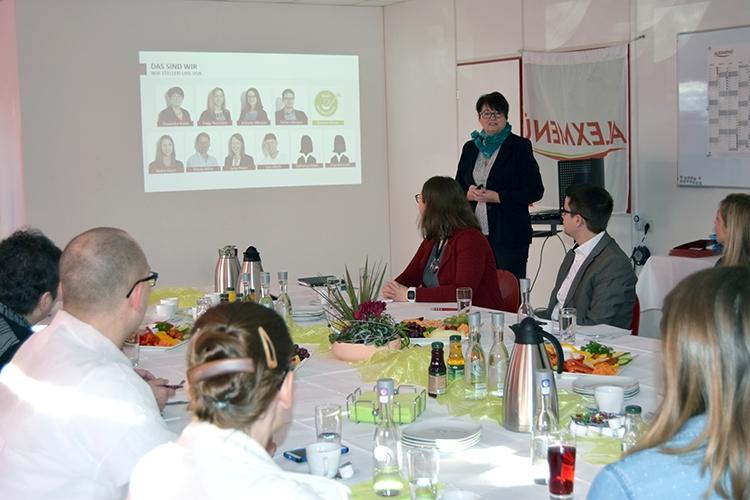 Frau Krotki, Geschäftsführerin von ALEXMENÜ, präsentiert die wichtigsten Fakten rund um das Unternehmen.