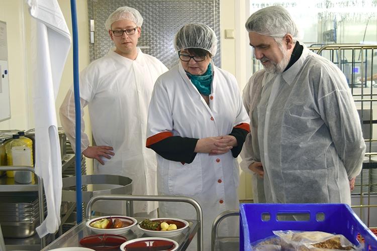 Herr Ullrich (Produktionsleitung), Frau Krotki (Geschäftsführung ALEXmENÜ) und Prof. Dr. Willingmann (Minister für Wirtschaft und Digitalisierung Sachsen-Anhalt) begutachten den Aufbau der Menüteller