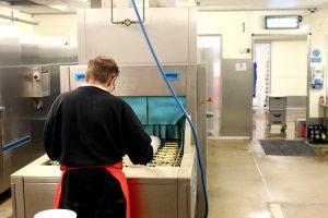 Ein Mitarbeiter befüllt fleißig die Bandspülanlage mit dem Geschirr.