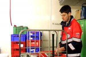 Ruben Hoffmann, Mitarbeiter der Maleser, hilft beim Sortieren des Geschirrs.