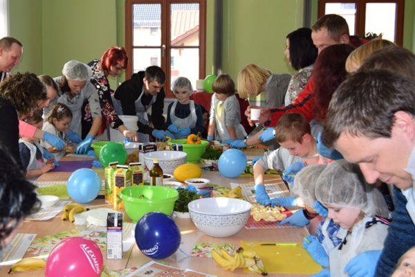 Alle großen und kleinen Teilnehmerinnen und Teilnehmer bereiten konzentriert die Zutaten für die Salate zu