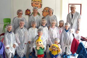 Kinder und Erzieher der Kita Körbelitz sehen sich die Produktionsräume von ALEXMENÜ an.