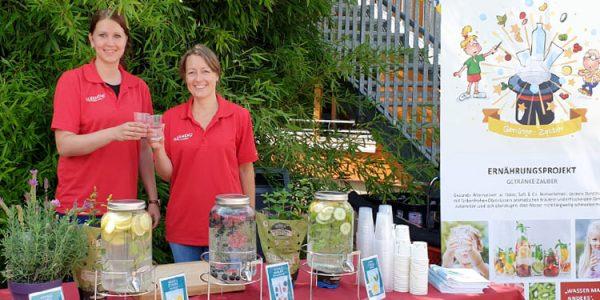 Diätassistenin Juliane Kumstel und Ernährungswissenschaftlerin Lydia Röder (v.l.) schenken aromatisiertes Wasser auf dem Schulfest aus.