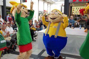 Die Maskottchen tanzen sich vor der großen Parade durch das Einkaufscenter schon mal warm.