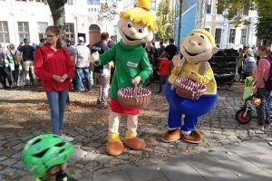 Die Maskottchen Hopsi und Klopsi feuern die Kinder beim Laufradrennen an und verteilen frische Äpfel.